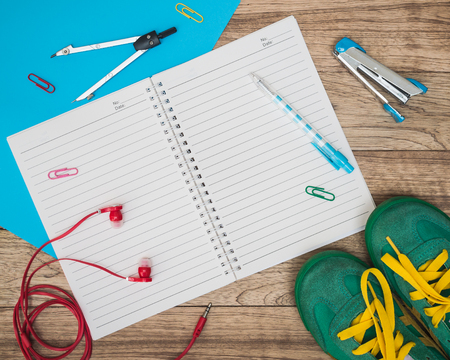Notebook, sneakers, earphones, paper, writing material and other on wooden plank, Education concept.