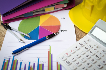 Finance graph with pen, construction helmet and calculator on table, Business and finance concept.