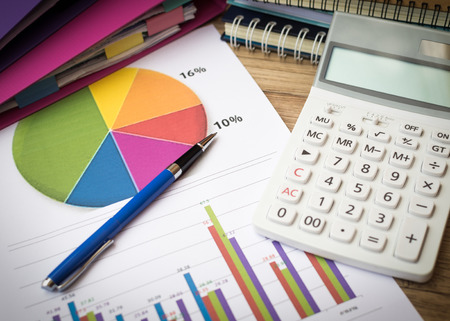 Finance graph with pen and calculator on table, Business and finance concept.