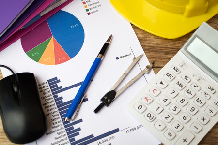 Finance graph with pen, construction helmet, calculator and other on table, Business and finance concept.