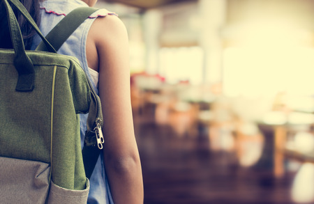 Girl with backpack entering to the classroom. Education concept. Stock Photo