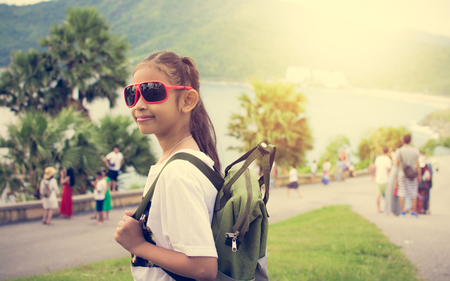 Cute girl with backpack at promthep cape with crowd of tourist under sunlight in phuket.
