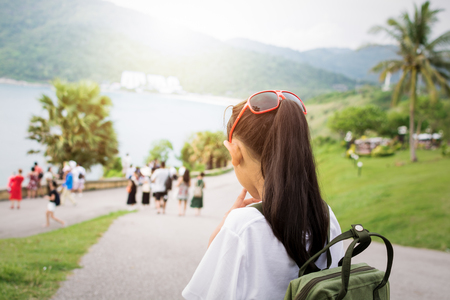 Cute girl with backpack viewing to the sea during sunset in phuket. Stock Photo