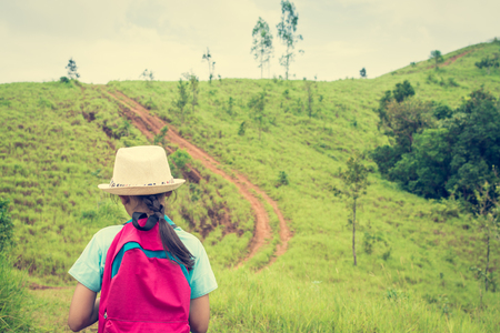 Girl with backpack walking in to bald hill during summer at Ranong Province, Thailand. Stock Photo