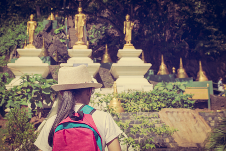 Girl with backpack entering to buddhist temple in Wat Tham Seua (Tiger Cave Temple) Krabi, Thailand.