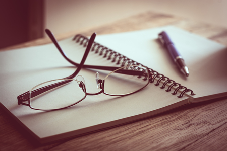 Glasses, notebook and pen on wooden table. Education concept.