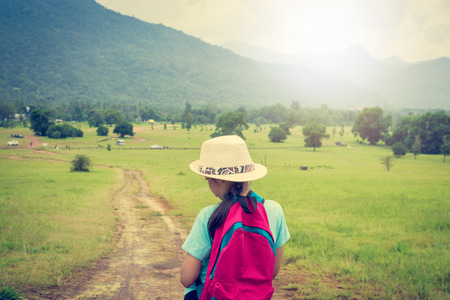Girl with backpack walking in the field during summer at Ranong Province, Thailand.