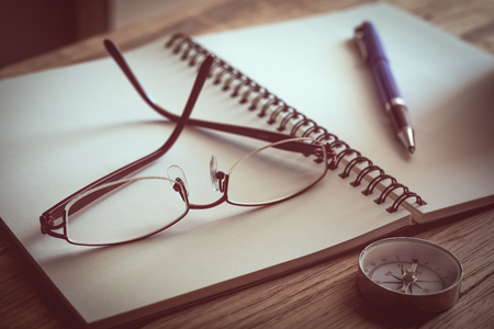 Glasses, notebook, pen and compass on wooden table. Education concept.
