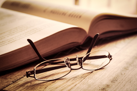 Old book with vintage glasses on a wooden table.
