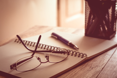 Glasses, notebook and pen on wooden table in warm tone.