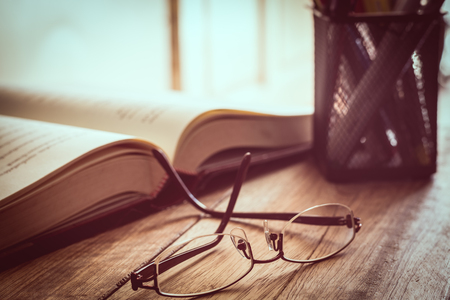 Glasses, book and writing material on wooden table. Education concept.