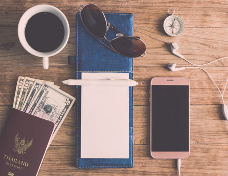Notebook, Pen, Sunglasses, Coffee Cup, Passport, Money, Mobile Phone, Earphones and Compass on wooden plank. Travel Concept. Stock Photo