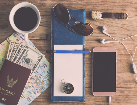 Notebook, Pen, Sunglasses, Coffee Cup, Passport, Money, Mobile Phone, Earphones, Map,  wristwatch and Compass on wooden plank. Travel Concept.