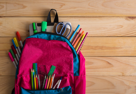 School backpack and school supplies on wooden table background. Back to school concept.
