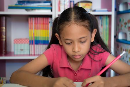 Little girl doing homework on table at home, Education concept.