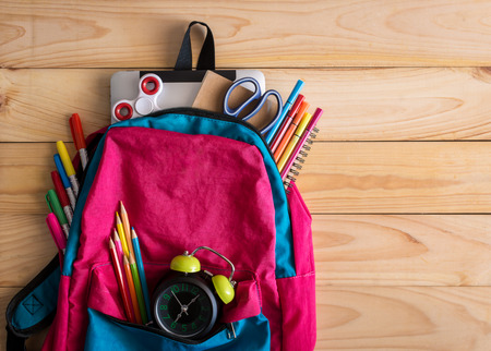 School backpack with school supplies and clock on wooden table background. Back to school concept. Stock Photo