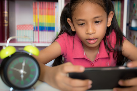 Little girl using mobile phone with wireless internet at home. Education concept.