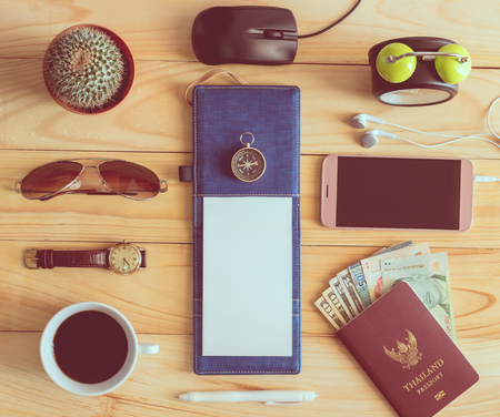 Top view of notebook, pen, sunglasses, coffee cup, passport, money, mobile phone, earphones, wristwatch, cactus, clock, computer mouse and compass on wooden table. Travel concept. Stock Photo