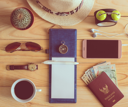 Top view of notebook, pen, sunglasses, coffee cup, passport, money, mobile phone, earphones, wristwatch, cactus, clock, straw hat and compass on wooden table. Travel concept.
