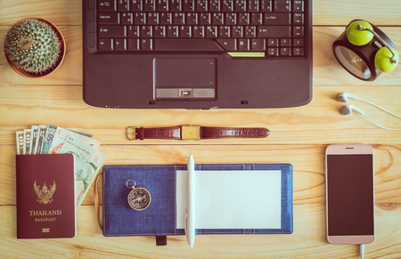 Top view of laptop, notebook, pen, passport, money, mobile phone, earphones, wristwatch, cactus, clock, and compass on wooden table in office. Business concept.