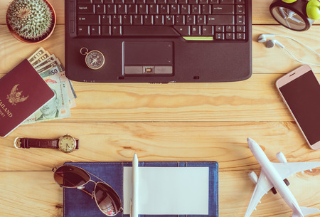 Top view of laptop, notebook, pen, sunglasses, passport, money, mobile phone, earphones, wristwatch, cactus, clock, airplane and compass on wooden table. Business concept.