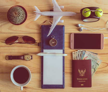 Top view of notebook, pen, sunglasses, coffee cup, passport, money, mobile phone, earphones, wristwatch, cactus, clock, airplane and compass on wooden table. Travel concept.
