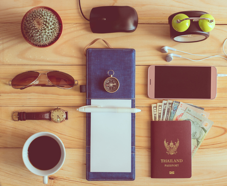 Top view of notebook, pen, sunglasses, coffee cup, passport, money, mobile phone, earphones, wristwatch, cactus, clock, computer mouse and compass on wooden table in office. Business concept. Stock Photo