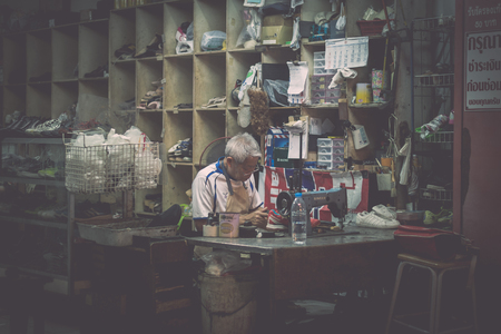 PHUKET, THAILAND-FEBRUARY 23, 2018 : Old shoemaker woking in his shop at night under light in phuket, Thailand. Editorial