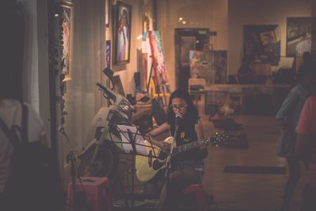 PHUKET, THAILAND-FEBRUARY 23, 2018 : Yong musician playing music in front of art shop at night, Phuket, Thailand. Editorial