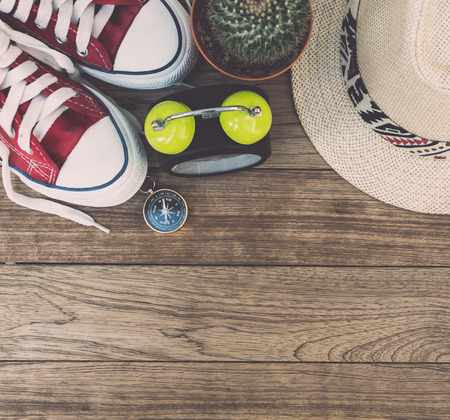 Top view of alarm clock, compass, cactus, sneakers and  straw hat on wooden table. Stock Photo