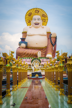 Giant smiling or happy buddha statue with blue sky in buddhist temple ( wat plai laem ), Koh Samui, Thailand. Stock Photo
