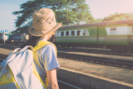 Young girl with bagpack waiting for a train at railway station in summer time. Stock Photo