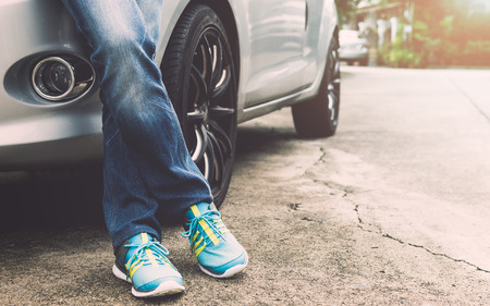Female traveller wearing jeans and sneakers standing beside the car.Travel concept.