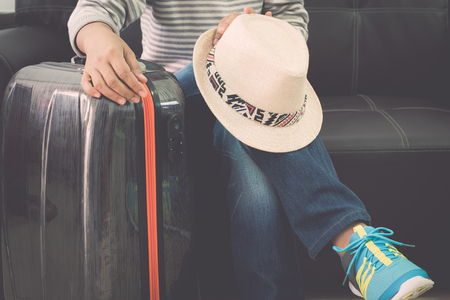 Female traveller is sitting with traveling bag and straw hat on leather sofa at the airport. Travel concept. Stock Photo
