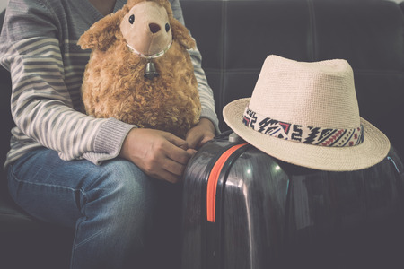 Female traveller with hers sheep doll, traveling bag and straw hat while waiting at the airport. Travel concept.