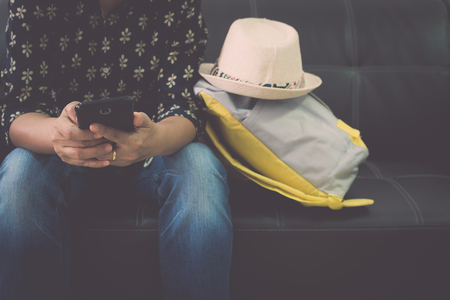 Female traveller is relaxing on leather sofa holding mobile phone at the airport. Travel concept.