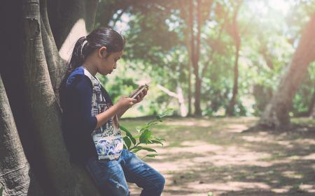 Girl using mobile phone under big tree in the garden under sunlight. Stock Photo