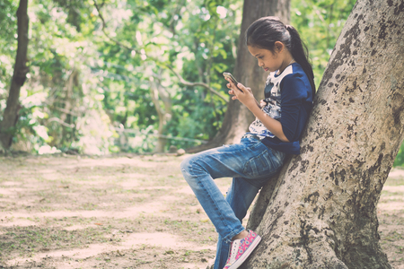 Young girl using mobile phone under big tree in the garden under sunlight.