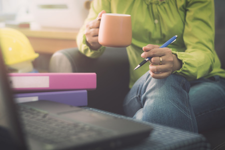 Businesswoman in casual dress holding coffee cup and pen while planning for online ordering with laptop via the internet. Business And Financial Concept.