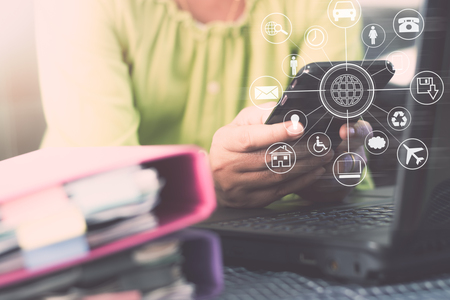 Hands of woman using mobile phone for payments online shopping with laptop and document on the table with virtual icon diagram. Business And Financial Concept. Stock Photo
