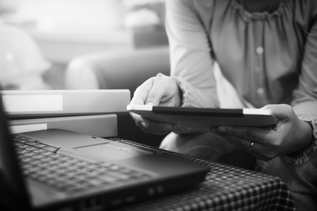 Businesswoman in casual dress holding tablet with online. while making orders via the Internet. Business And Financial Concept. Black and white picture.