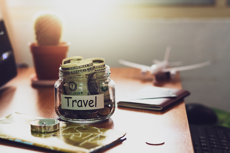 Travel budget concept. Money for Travel savings in a glass jar with compass, passport, credit card, aircraft toy and world map on working desk.