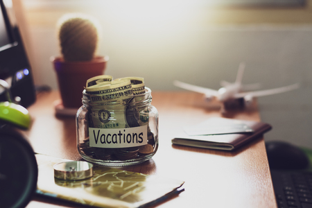 Vacation budget concept. Money for vacations savings in a glass jar with compass, passport, clock, credit card, aircraft toy and world map on working desk. Stock Photo