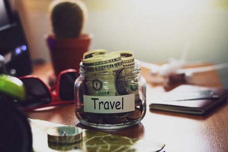 Travel budget concept. Money for Travel savings in a glass jar with compass, passport, credit card, aircraft toy, sunglasses and world map on working desk. Stock Photo