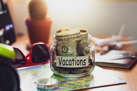 Vacation budget concept. Money for vacations savings in a glass jar with compass, passport, sunglasses, credit card and aircraft toy on world map