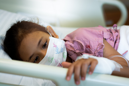 Little girl patients wearing protective mask in the hospital. Healthcare and medical concept.