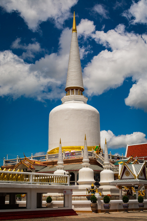 Huge holy pagoda in buddhist temple with cloudy blue sky, Thailand. Stock Photo