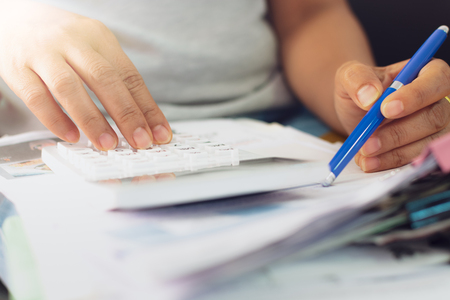 Hands of woman is calculating expenses documents at home, Business concept.