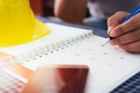 Hands of female architect is planning and managing work on the calendar, Planning concept. Stock Photo
