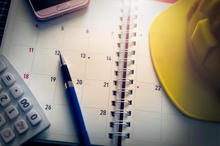 Notebook calendar with pen, mobilephone, calculator and construction helmet on the desk under light.